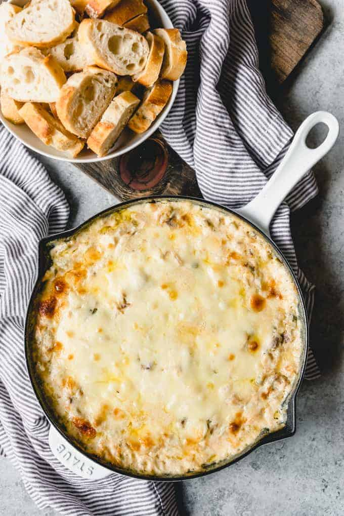 An image of a Philly Cheese Steak Dip recipe in a cast iron skillet right after coming out of the oven when the cheese on top is melted and slightly browned.