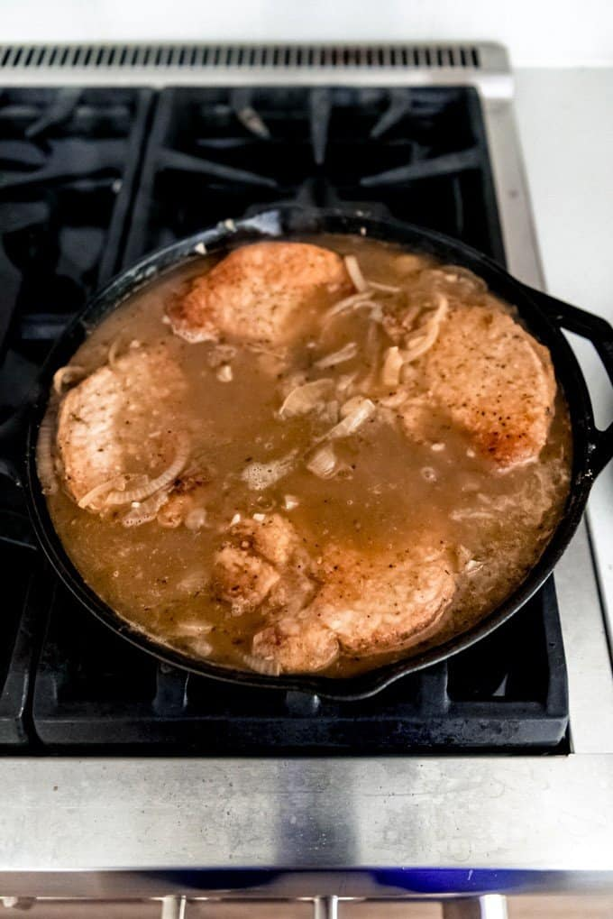 An image of pork chops in gravy in a cast iron skillet.