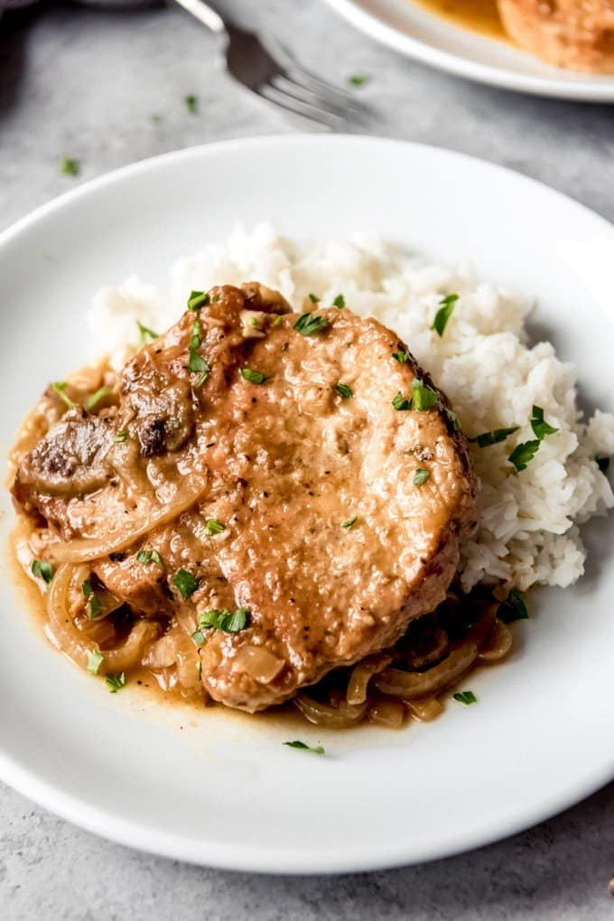 An image of bone-in pork chops with gravy and rice on a plate.