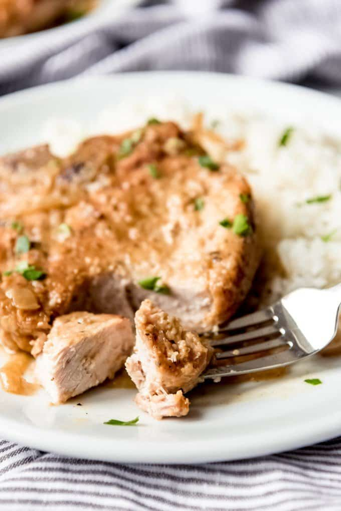 An image of tender pork chops with onion gravy on a plate with white rice.