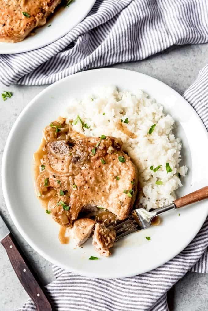 An image of a plate of Southern Smothered Pork Chops with rice.
