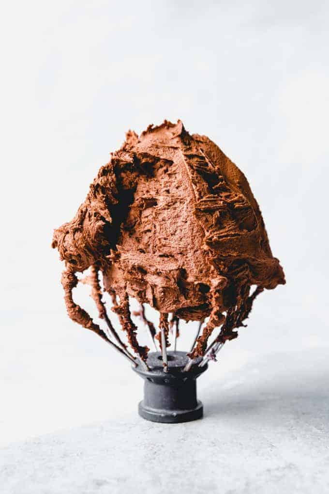 An image of a Kitchenaid whisk attachment covered in chocolate buttercream frosting.