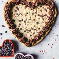 An aerial view of a heart shaped giant chocolate cookie with frosting and sprinkles and heart shaped bowls filled with chocolate chips to the side