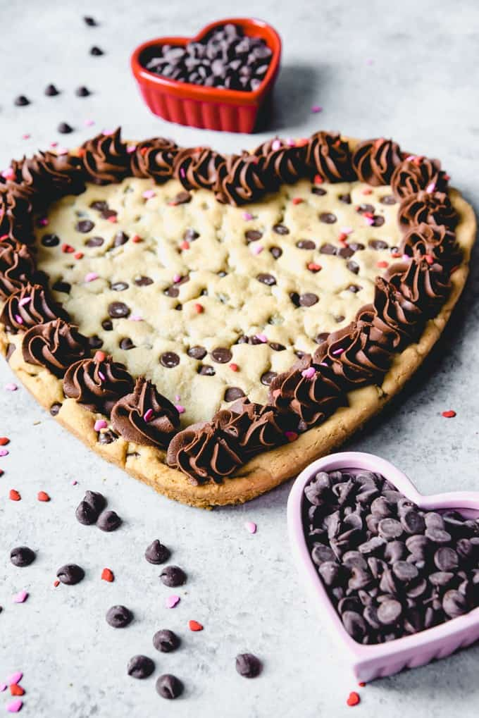 An image of a giant heart-shaped Valentine's Day cookie decorated with sprinkles and chocolate frosting.