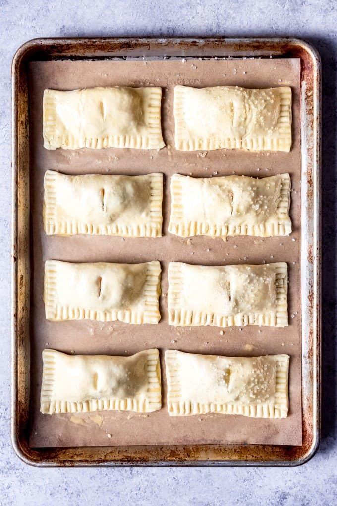 An image of 8 cuban pastries made with guava paste, cream cheese, and puff pastry, on a baking sheet.