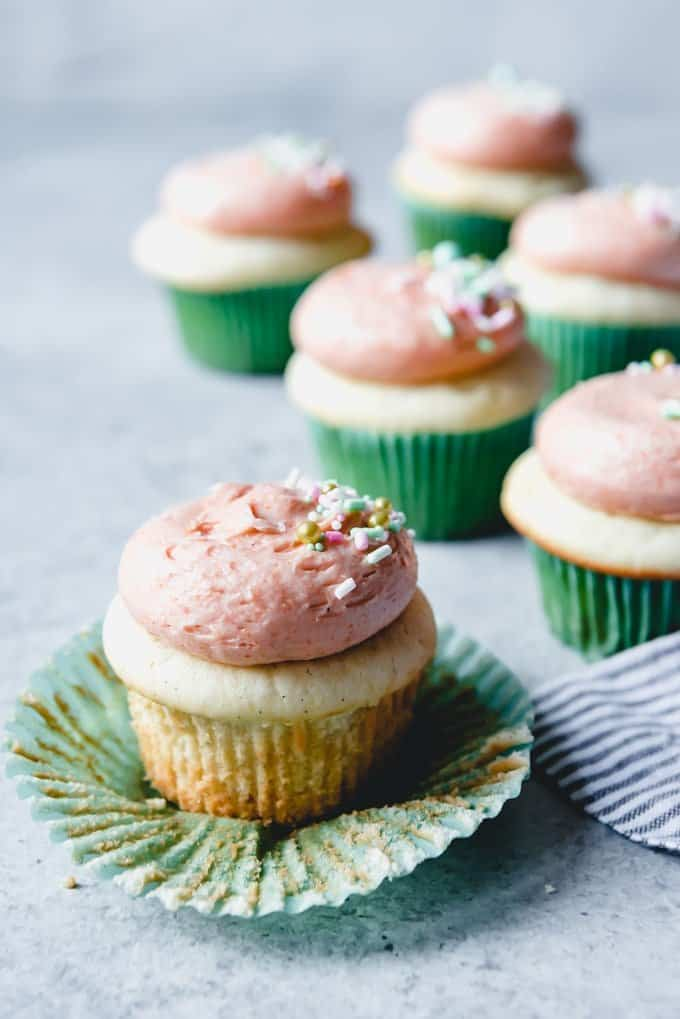 An image of an unwrapped cupcake frosting with guava buttercream frosting.