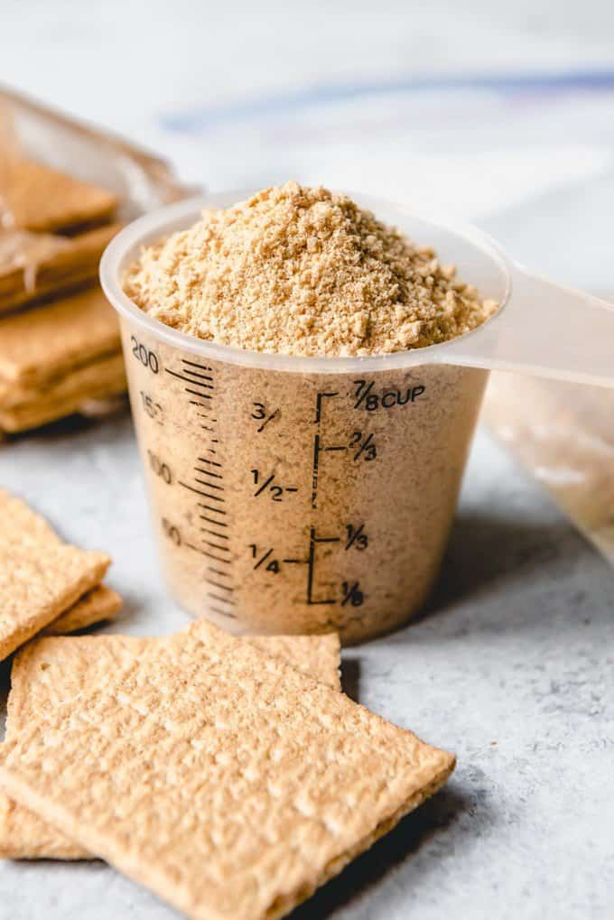 An image of graham cracker crumbs in a measuring cup for a graham cracker crust for key lime pie.