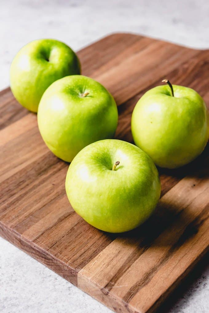 An image of four granny smith apples on a wooden cutting board.