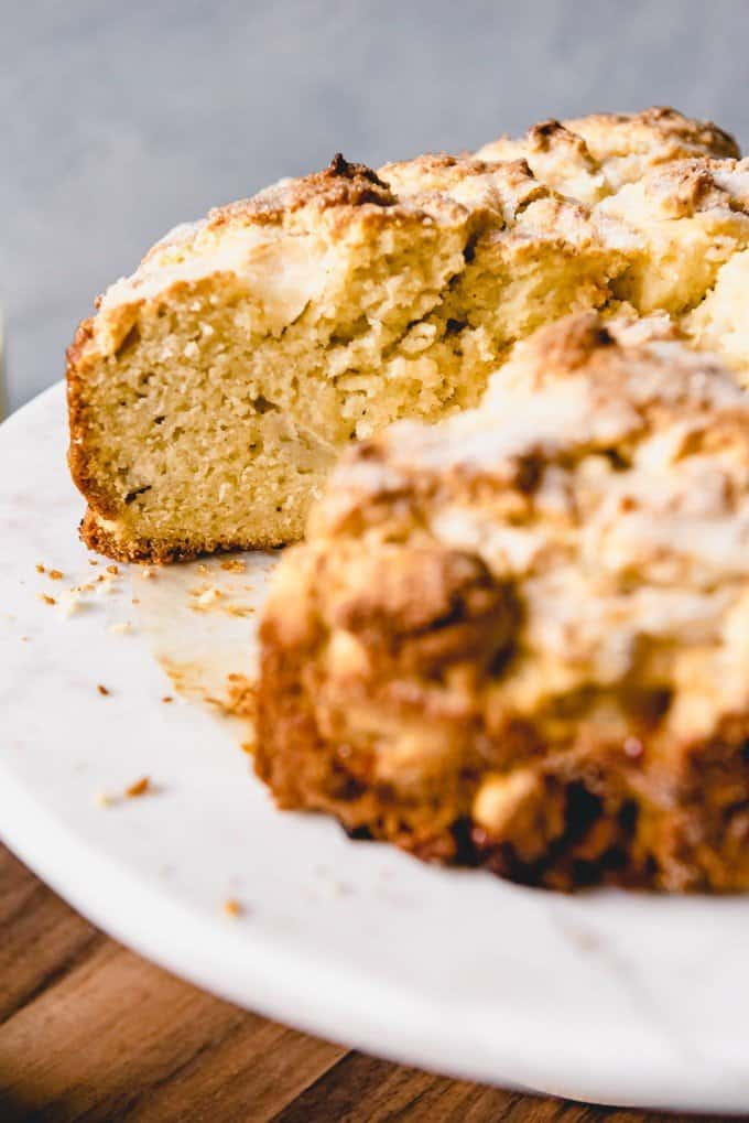 An image of the texture of a sliced Irish apple cake on a marble cake stand.