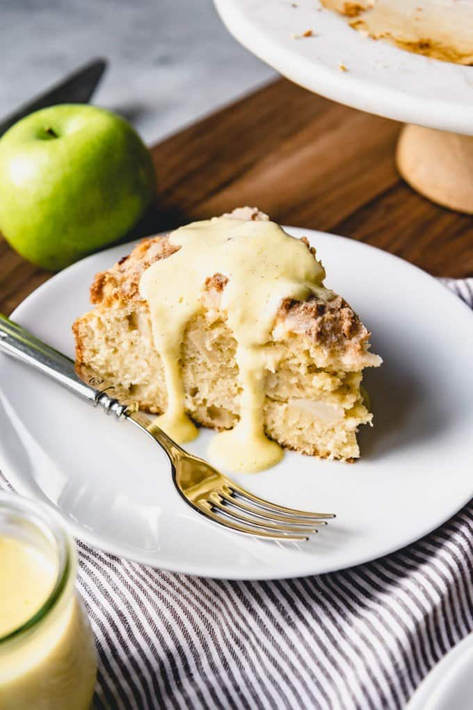 An image of a slice of Irish apple cake, or Kerry apple cake, with vanilla custard sauce drizzled over the top of it.