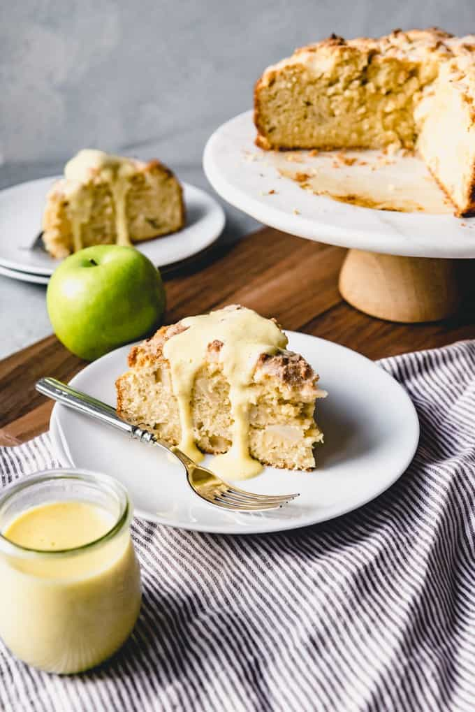 sliced irish applecake with custard on white plates below a cake stand with more cake on it and a green apple and jar of custrd resting to the side