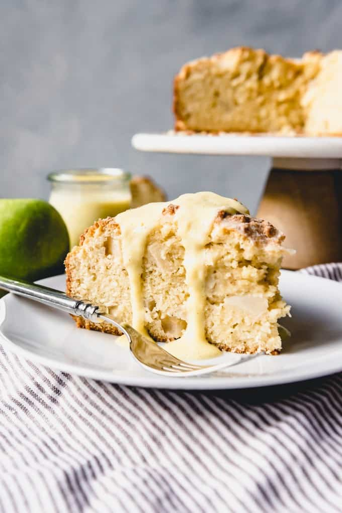 An image of a slice of Irish apple cake with creme anglaise on top.