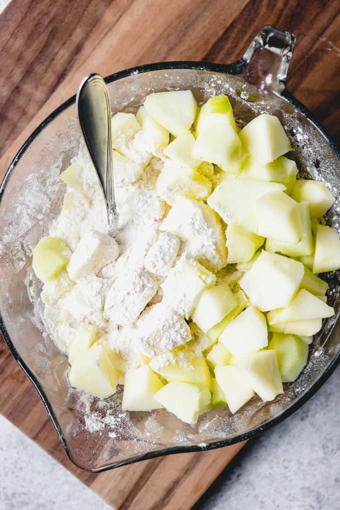 An image of chunks of granny smith apple being added to flour and other ingredients for making an Irish apple cake.