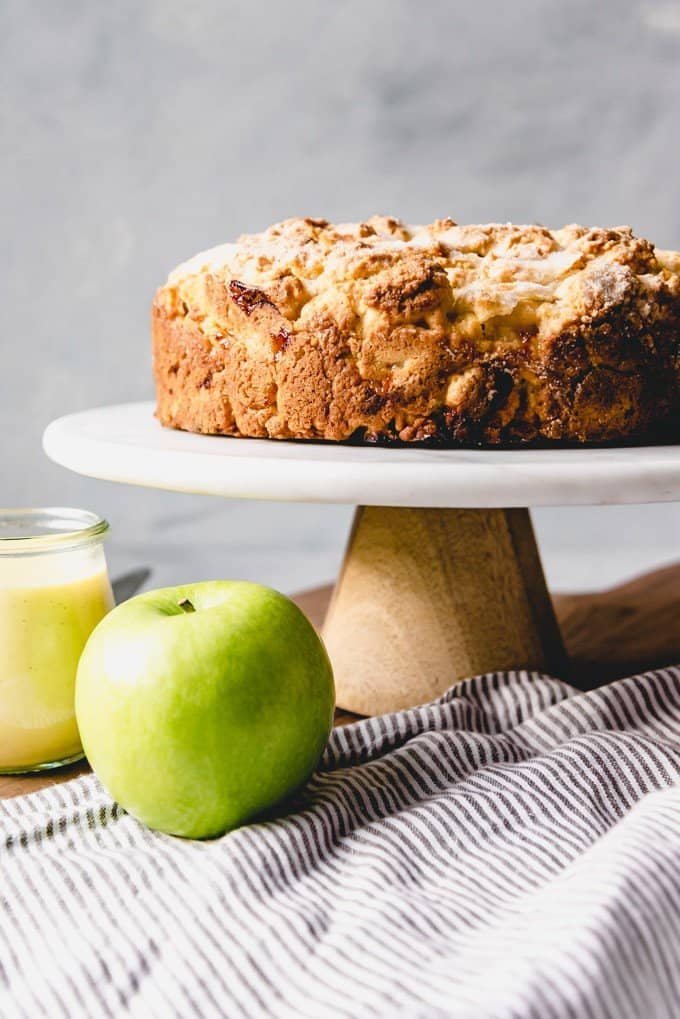 An image of an Irish apple cake on a cake stand with an apple and vanilla custard sauce next to it.