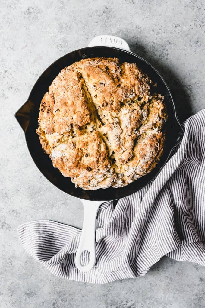 An image of Irish soda bread with raisins in a cast iron pan.