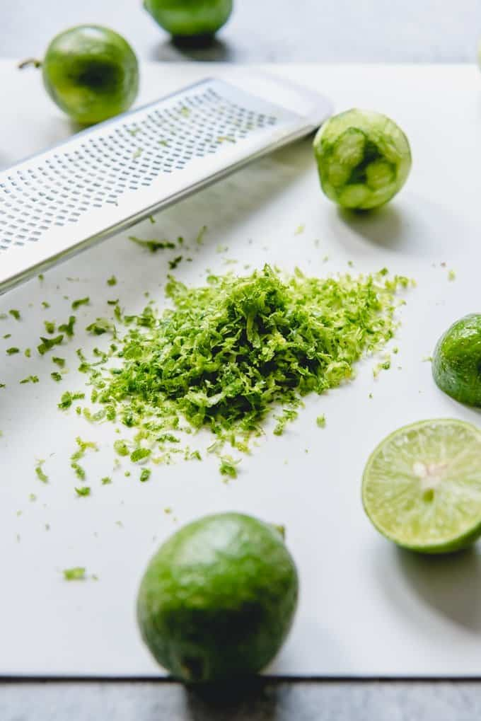 An image of key lime zest next to a zester and sliced key limes for juicing.