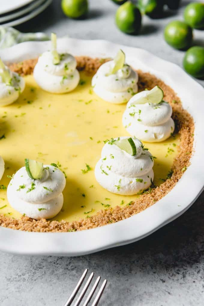 An image of a homemadde Florida key lime pie made from scratch and topped with whipped cream swirls and thin slices of key limes.