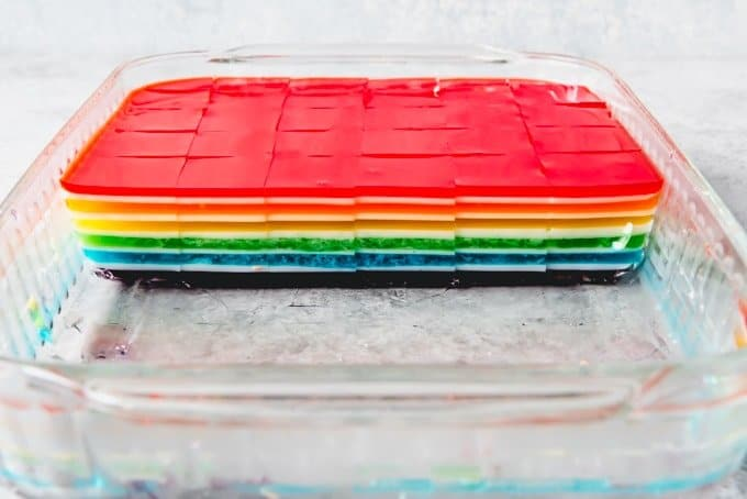 An image of a pan of sliced finger jello cubes made with layers of flavor and colors of the rainbow.