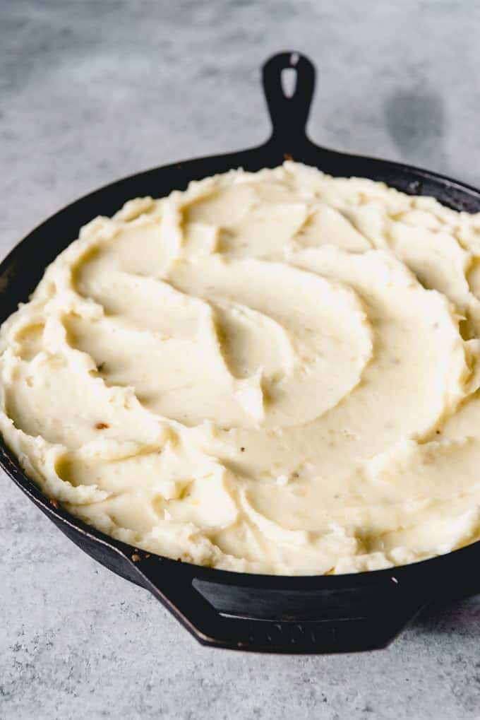 An image of mashed potatoes on top of a savory lamb filling for a classic shepherd's pie recipe.