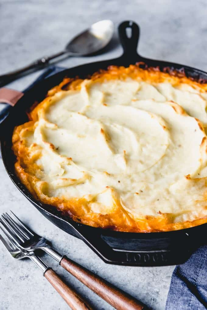 An image of a baked shepherd's pie in a cast in pan ready for serving with creamy swirls of golden brown mashed potatoes on top.