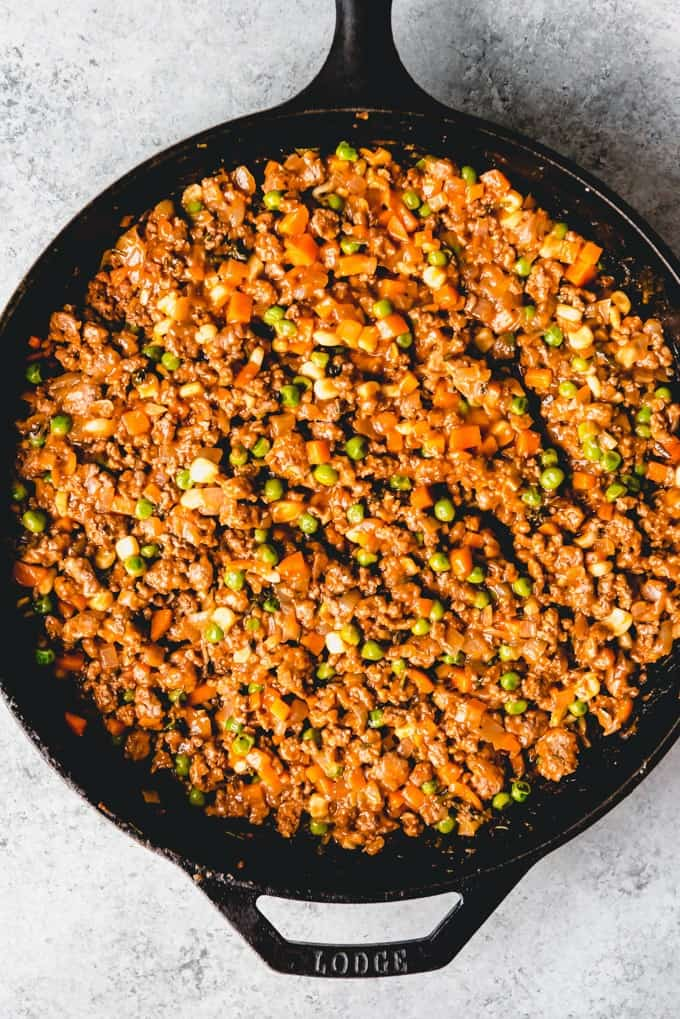 An image of the best shepherd's pie filling in a cast iron pan, ready to be topped with creamy mashed potatoes and baked until hot and bubbly.