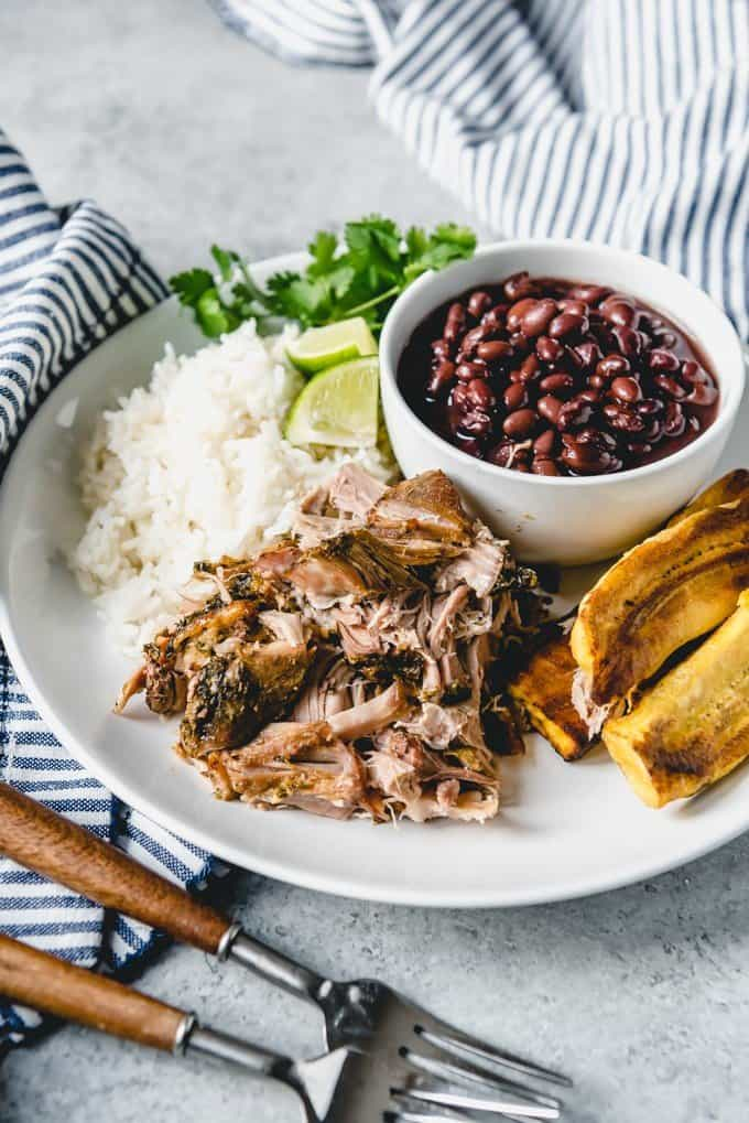 An image of a plate of Slow Cooker Cuban Mojo Pork with rice and beans on the side.