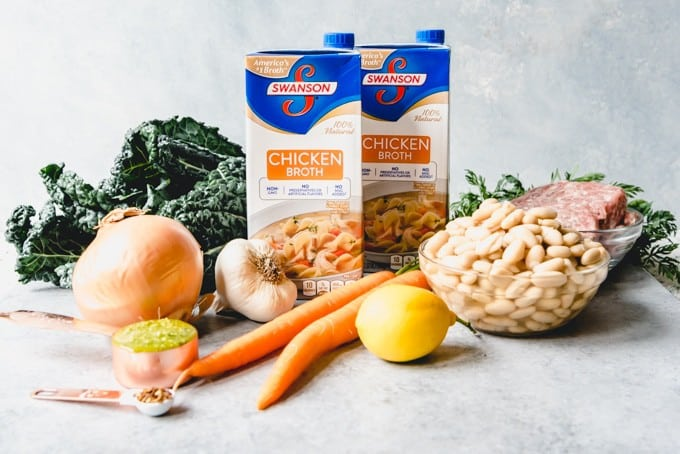 An image of the ingredients for Tuscan white bean soup including carrots, onions, garlic, kale, cannellini beans, Italian sausage, lemon juice, and chicken broth.