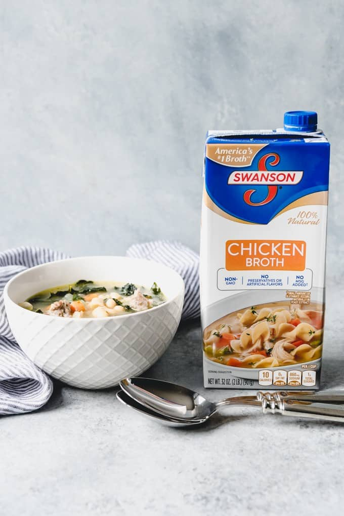 An image of a bowl of slow cooker Tuscan white bean soup next to a carton of Swanson Chicken Broth.