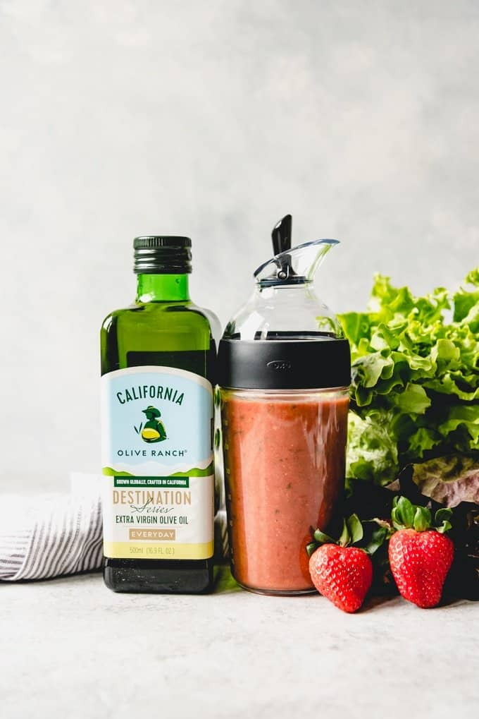 An image of a bottle of California Olive Ranch Extra Virgin Olive Oil next to a salad dressing shaker jar of homemade strawberry balsamic vinaigrette.