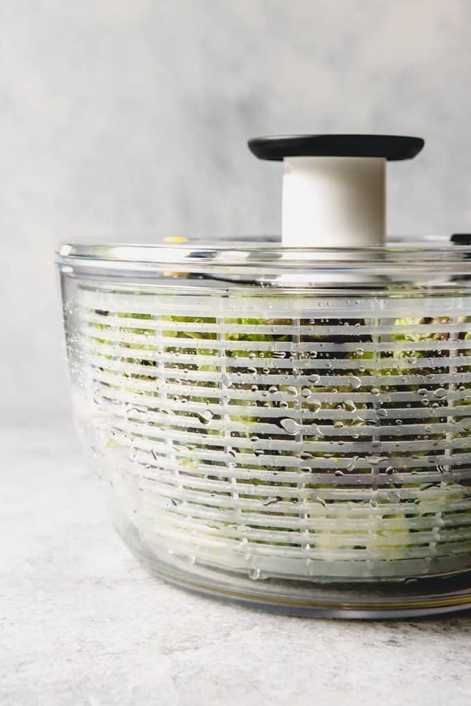 An image of a salad spinner filled with mixed lettuce greens with water droplets on the side.