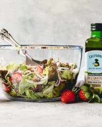 a large glass bowl filled with Spring Salad with Strawberry Balsamic Vinaigrette in a shaker to the side and bottles of olive oil on the other side
