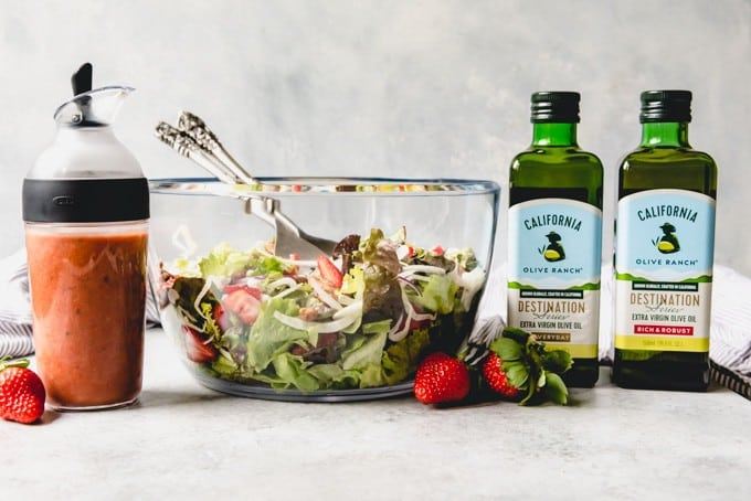 An image of a mixed greens salad with shaved fennel, goat cheese, strawberries, and candied walnuts, next to a jar of strawberry balsamic vinaigrette and bottles of olive oil.