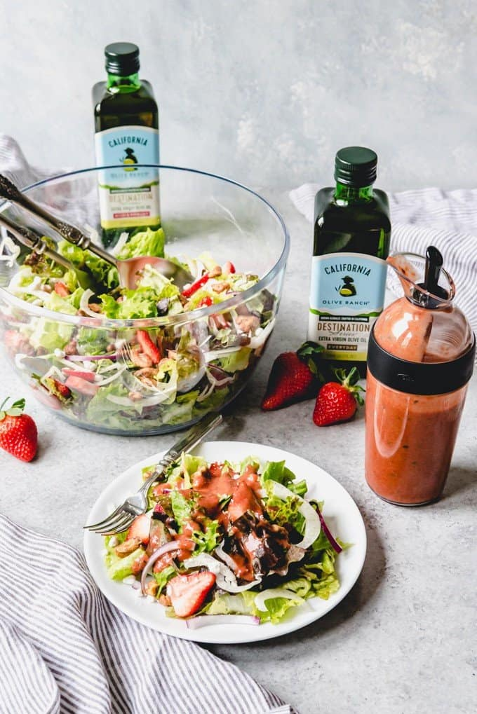An image of a bowl of strawberry Spring salad with serving spoons next to a plate of salad drizzled with strawberry balsamic vinaigrette.