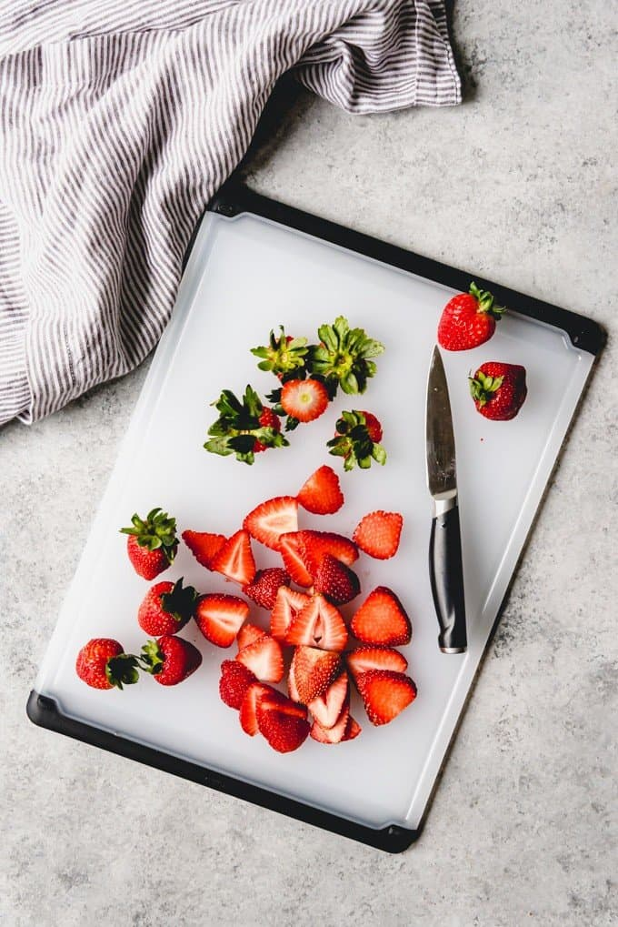 An image of sliced strawberries on a cutting board with a paring knife.
