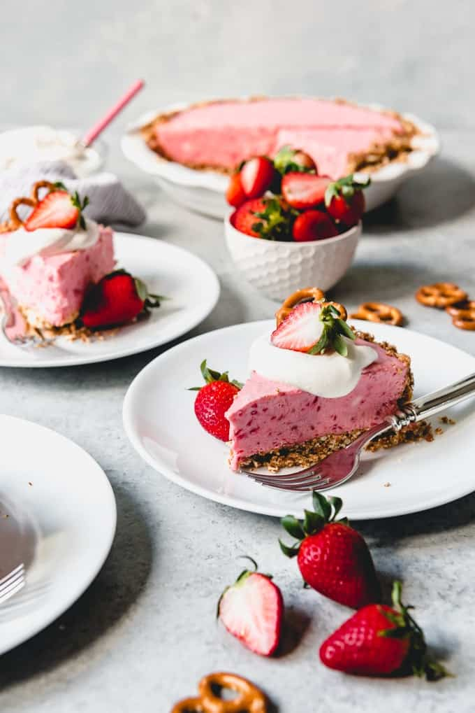 You will want to make this crowd-pleasing Strawberry Pretzel Icebox Pie all Spring and Summer long!  It's a delicious frozen dessert made with a strawberry cream cheese filling inside a salty-sweet pretzel crust.  Then the fluffy pink pie is topped with clouds of freshly whipped cream for a simple but tasty dessert that is perfect for Valentine's Day, Easter, Mother's Day or basically any time the weather gets warm!