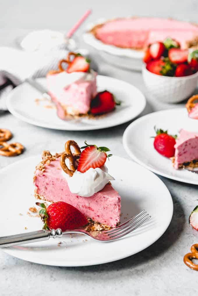 An image of a strawberry pie recipe with a pretzel crust, sliced and served on white plates with freshly whipped cream, pretzels, and strawberry halves on top.