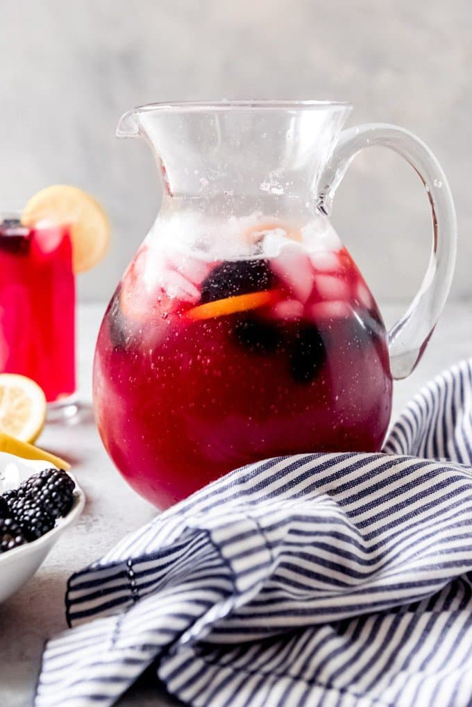 An image of a glass pitcher filled with fresh squeezed blackberry lemonade.