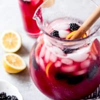 blackberry lemonade in a pitcher with fresh lemon slices and blackberries and a filled cup in back