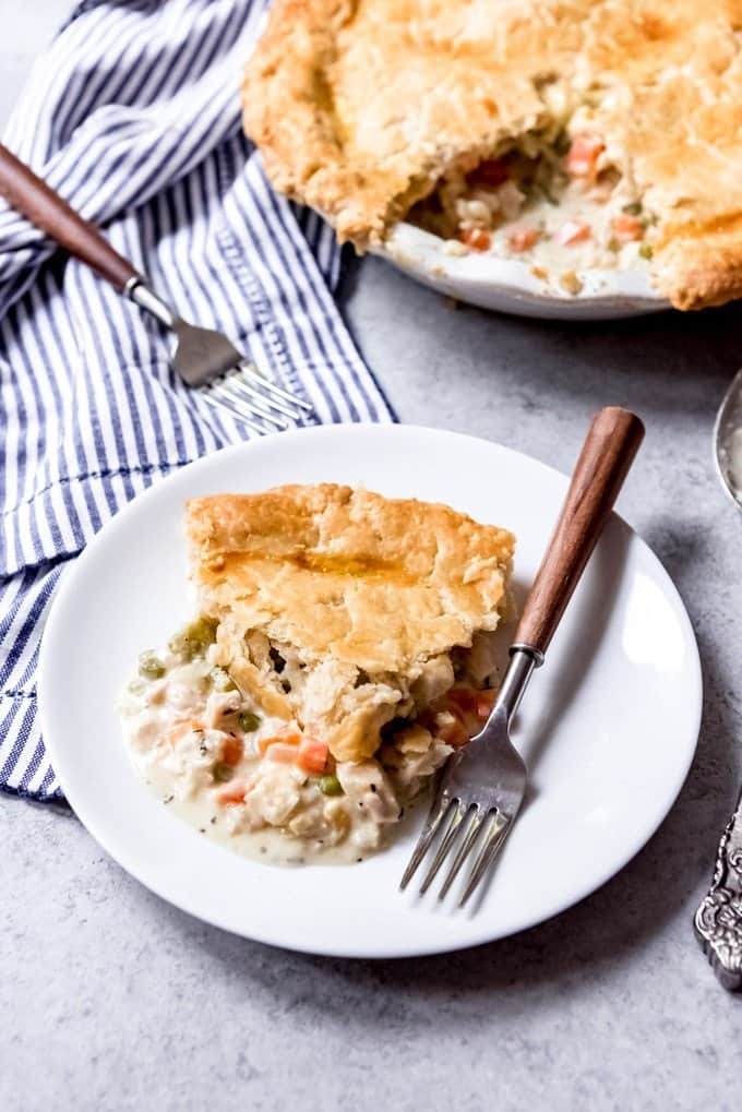An image of a piece of chicken pot pie on a plate with a fork with the rest of the pot pie next to it.