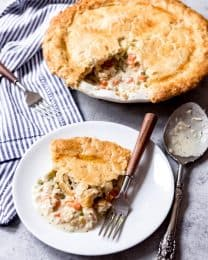 a white plate with a slice of chicken pot pie and a fork in front of a chicken pot pie missing a slice