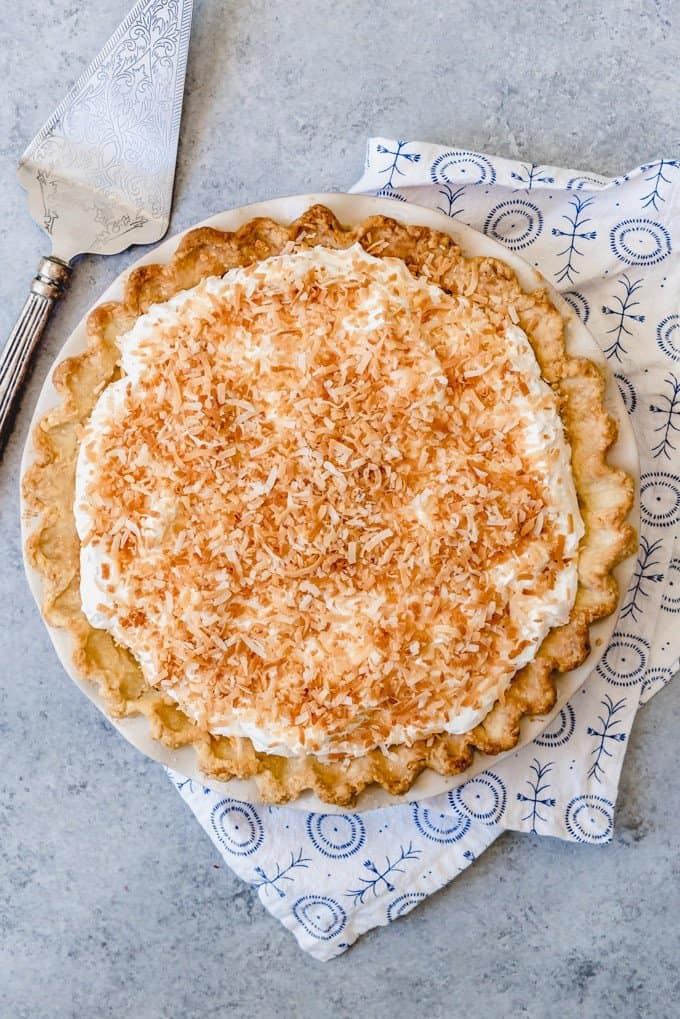 An image of a homemade coconut cream pie made from scratch, covered in toasted coconut.