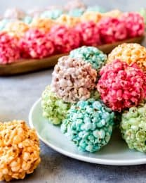 Children and grown-ups alike will love these easy Marshmallow Popcorn Balls that you can make with all the colors of the rainbow!  They are perfect for Spring or just about any holiday and so much fun to make!