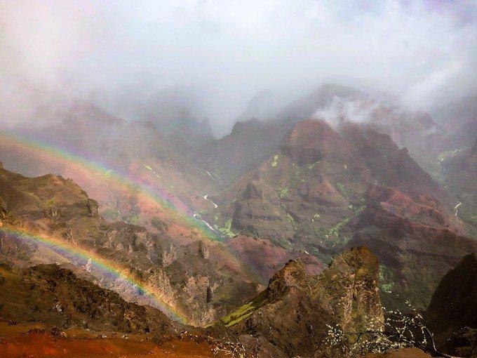 double rainbow near some sharp hills