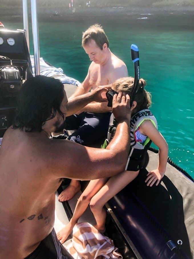 a man applying scuba headset to a girl