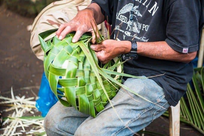 a man carefully weaving a green basket