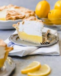 a slice of lemon meringue pie on a gray plate with a fork and sliced and whole lemons on the right with more pie on the left