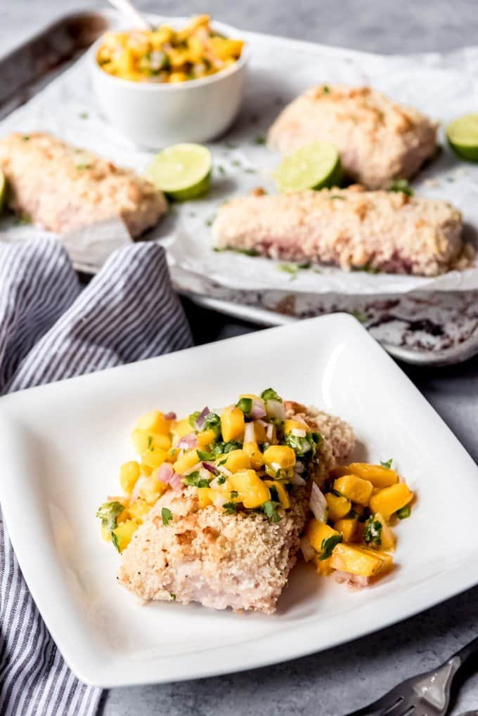 An image of a fillet of fish on a white plate topped with mango salsa and a nutty breadcrumb coating on the outside.