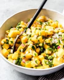 a spoon in a bowl of mango salsa