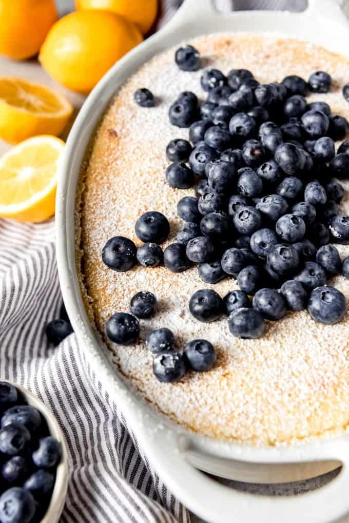 An image of a homemade lemon pudding cake topped with fresh blueberries and powdered sugar.