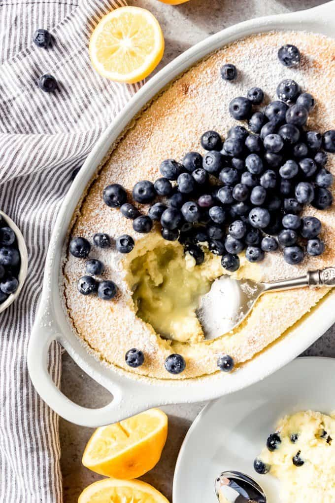An image of a meyer lemon pudding cake topped with blueberries, with a big scoop taken out of the middle.